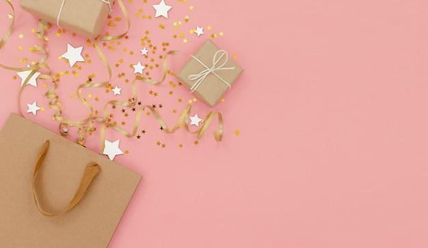 紙吹雪、プレゼントと弓、トップ水平ビュー付きバッグ。新年とクリスマスのお祭りの背景。休日、ショッピング、販売のコンセプト。