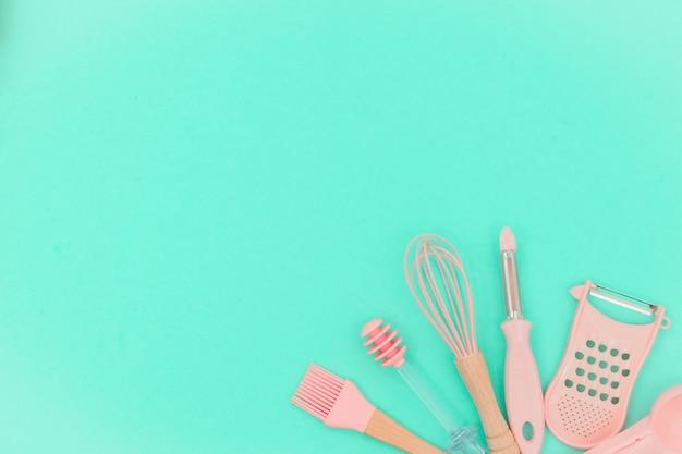 ネオミントの背景にピンクの台所用品。より大きく、泡立て器と鉄の調理形態。上面図