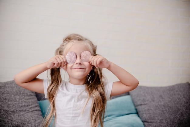 Маленькая девочка держит ракушки и мечтает о летнем призвании.