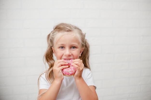 甘いピンクの艶をかけられたドーナツを食べるかわいい子供の女の子。