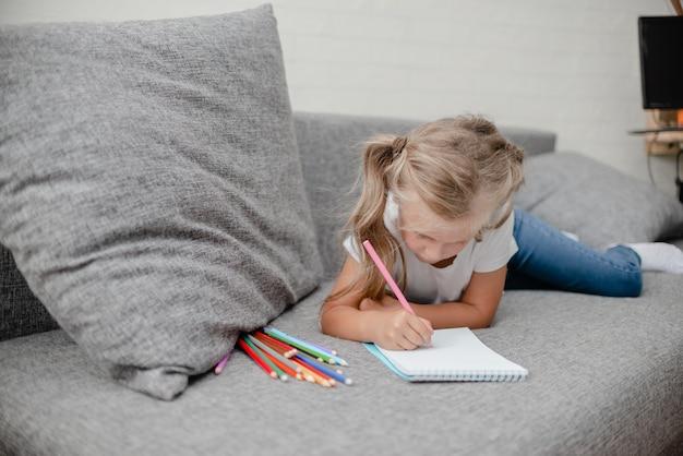 リビングルームのソファに横たわって描く小さな子供。
