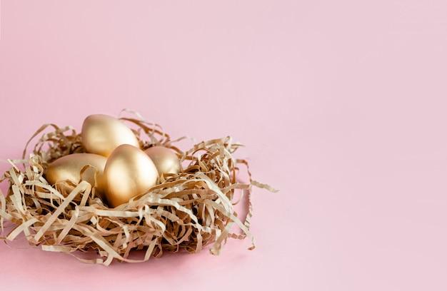 白い背景の上の巣で黄金のイースターエッグ装飾。テキストの最小限のイースターコンセプトコピースペース。トップ水平ビュー、フラットレイ。