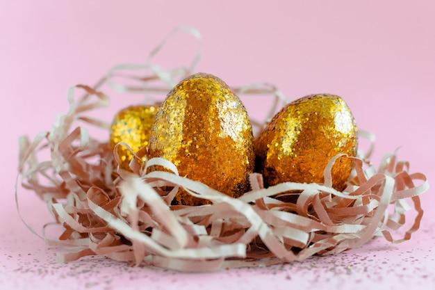 ピンクの背景の巣に黄金のイースターエッグが飾られています。テキストの最小限のイースターコンセプトコピースペース。