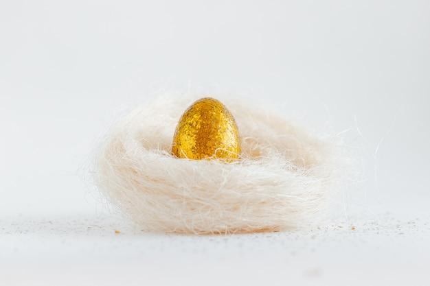 白い背景の上の巣で黄金のイースターエッグ装飾。テキストの最小限のイースターコンセプトコピースペース。