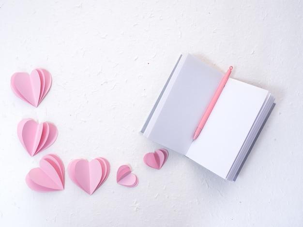 ピンクの紙の心を持つノートブック