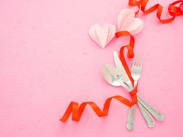 Столовые приборы и сердца на розовом столе