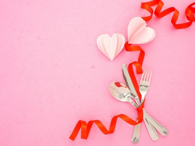 カトラリーとピンクのテーブルの上の心