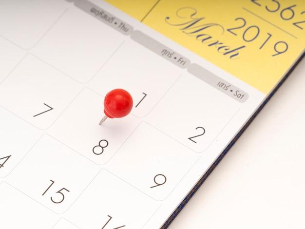 赤いピンとカレンダーの女性の日。