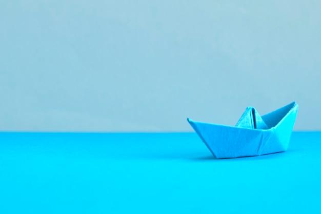 シアンの背景に青い紙のボート。リーダーシップ、マネジメント、ビジネス、モチベーションのコンセプト