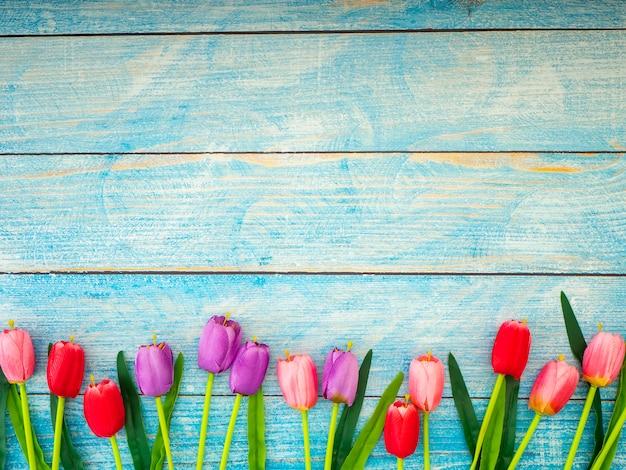 青い木製の背景にチューリップ