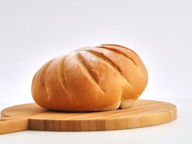 木製のボードの白い背景に隔離された新鮮なパン