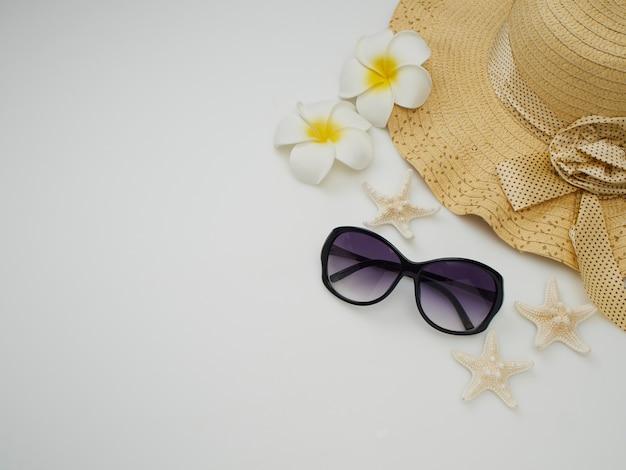 Летние пляжные наряды - ракушки, морские звезды, солнцезащитные очки, соломенные шляпы на белом фоне