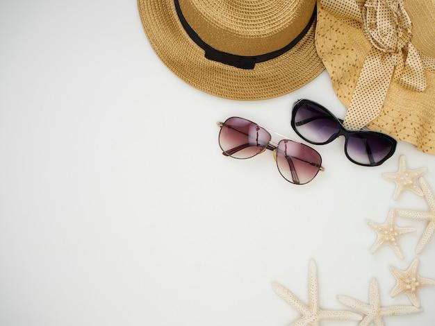 Раковины, морские звезды, соломенные шляпы, солнцезащитные очки на белом фоне