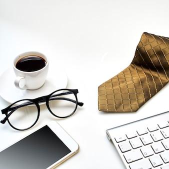 一杯のコーヒー、ネクタイ、その他の備品を備えたモダンな白いオフィスデスクトップテーブル。