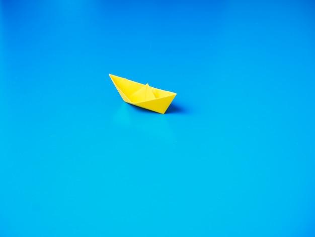 Бумажный кораблик на синем фоне бумаги