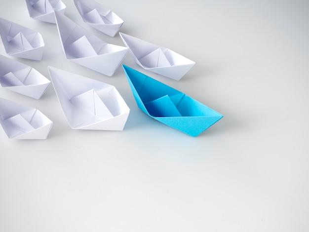 白い船の間を導く青い紙のボート