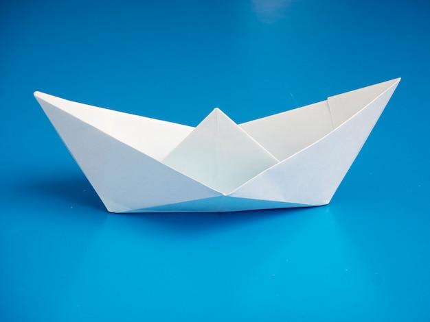 ビジネスコンセプト折り紙青い背景に最小限の白いボート紙
