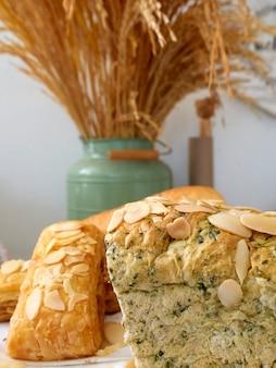 木製トレイと小麦の穀物の新鮮なベーカリー製品、テーブル、白いリネンの上に配置