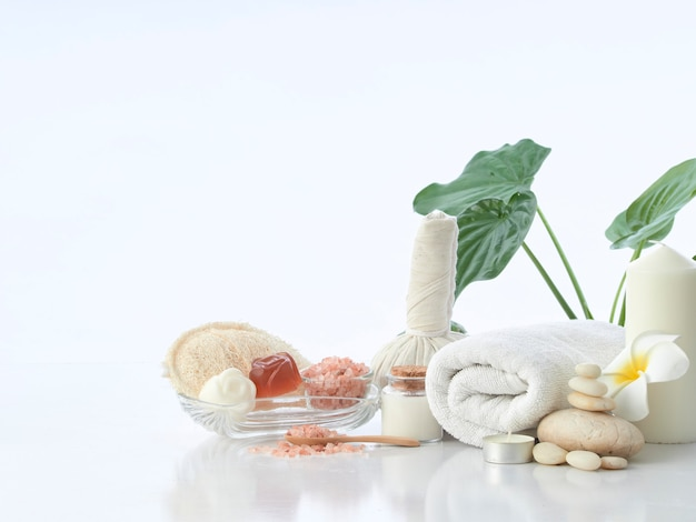 スパマッサージのコンセプト、ハーブの湿布ボール、クリーム、花の石鹸、香りのキャンドル、白で隔離されるヒマラヤピンクの塩
