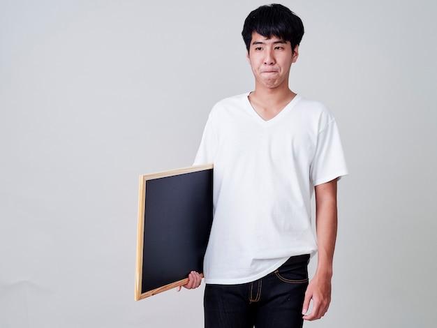 空の黒板を保持している若い男