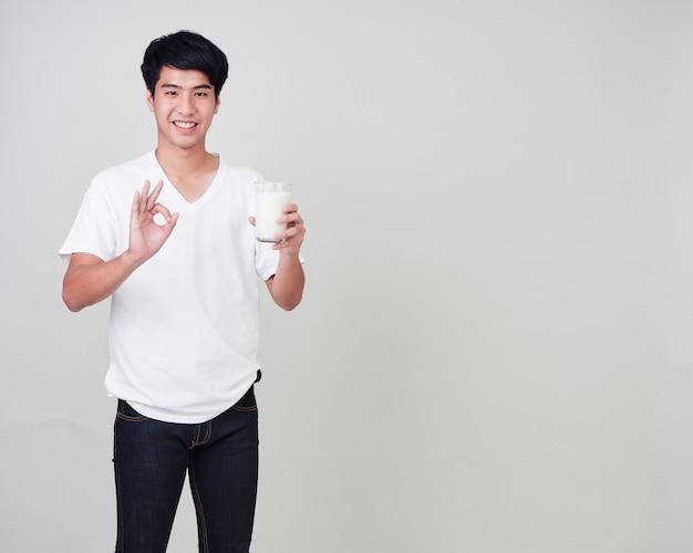 新鮮な牛乳のガラスを保持している若い男。