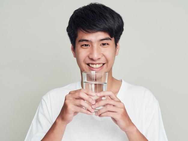 Молодой улыбающийся человек, держащий стакан воды