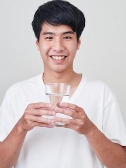 水のガラスを保持している若い笑みを浮かべて男