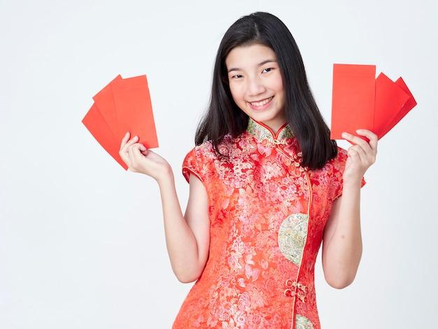 赤い封筒を保持している伝統的なチャイナドレスの女性