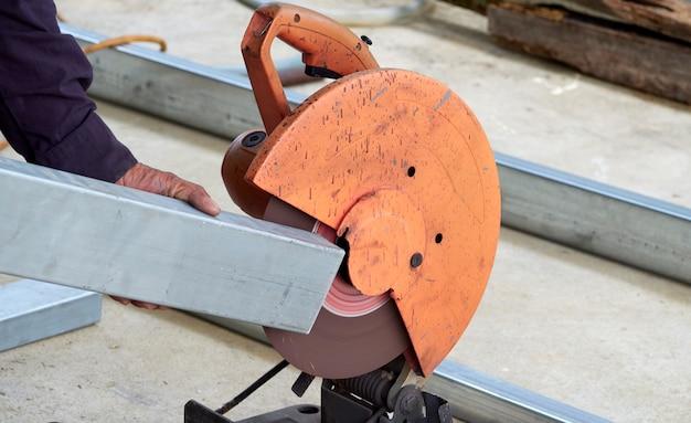 Рабочий режет железо с помощью отрезных кругов.