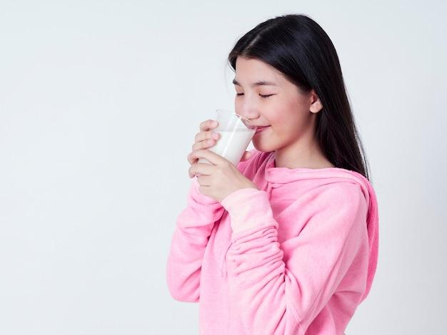 陽気な女の子が新鮮な牛乳を飲みます。