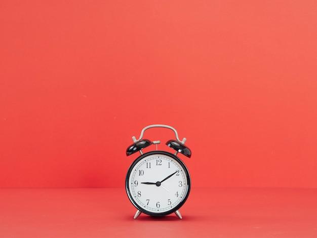 赤の背景に黒の目覚まし時計