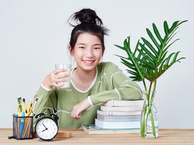 Милая девушка держит стакан молока.