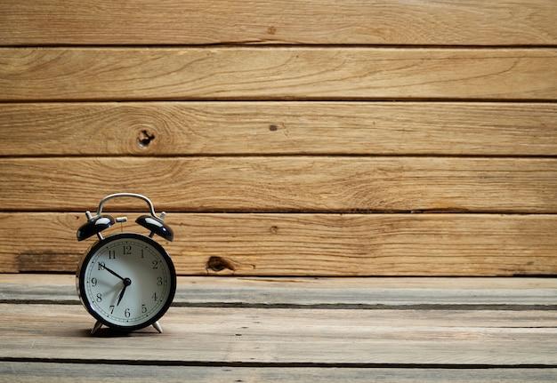 木製の背景に黒の目覚まし時計。