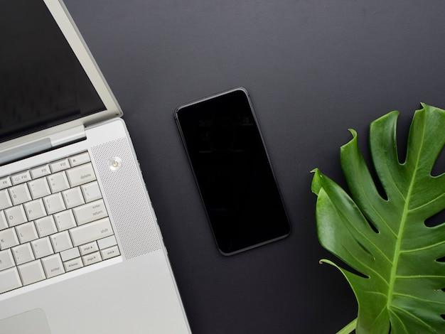 Ноутбук и смартфоны на офисном столе.