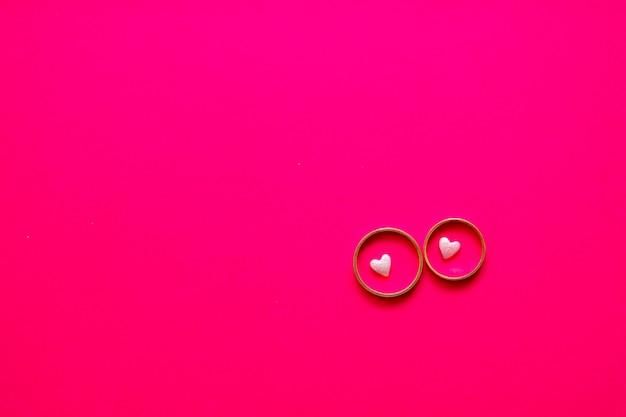 コピースペースとピンクの背景の結婚指輪