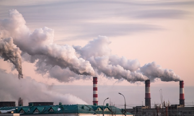 ピンクの夕焼け空の生態学的問題として大気汚染を引き起こす重煙の産業煙突