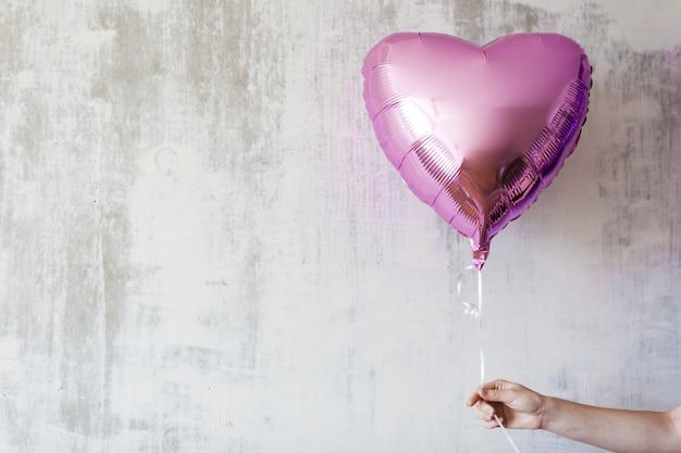 Рука вонана держит воздушный шар с розовым сердцем на сером бетонном фоне