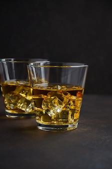 古い、錆びた背景に氷のウィスキーのガラス。