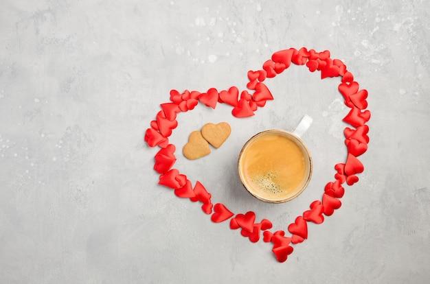 灰色のコンクリートの背景に新鮮な朝のコーヒーのカップ。バレンタインデーのコンセプト。