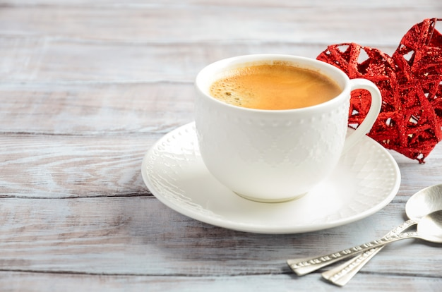 木製の背景に新鮮な朝のコーヒーのカップ。バレンタインデーのコンセプト。