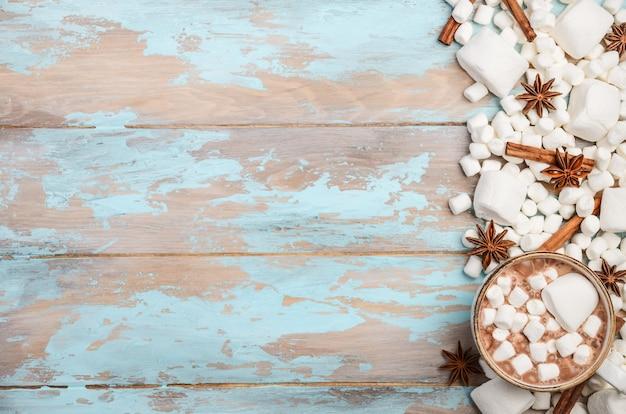 ホットチョコレート、ホワイトマシュマロ、青い木製の背景に冬のスパイス