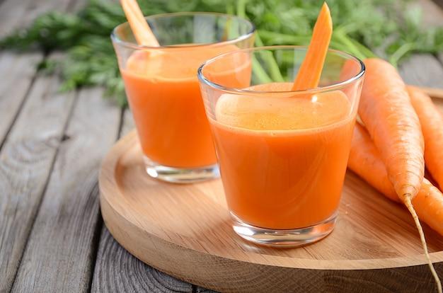 木製のテーブルに新鮮なにんじんジュース。