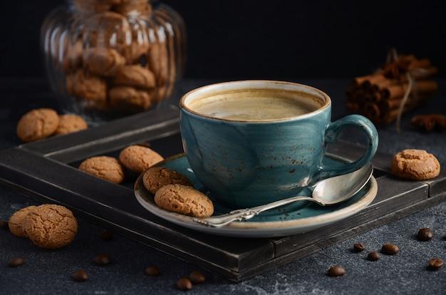 暗い背景にアマレッティクッキーと新鮮なコーヒーのカップ。