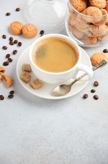 灰色のコンクリートのアマレッティクッキーと新鮮なコーヒーのカップ