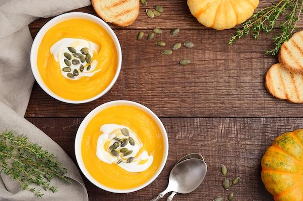 古い素朴なテーブルの上のクリームとカボチャの種のカボチャのクリームスープ。