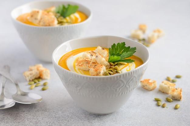 灰色のコンクリートまたは石の上にクリーム、クルトン、カボチャの種、パセリを添えたカボチャのスープ。