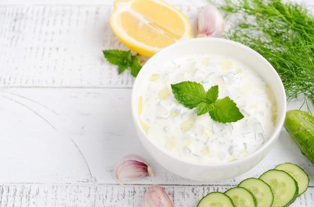 ギリシャのディップソースまたはドレッシングのザジキとオリーブオイルと白い木製のテーブルにミントで飾られた食材