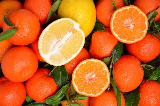 新鮮なタンジェリンクレメンタインとレモンの葉と木製の背景トップビュー