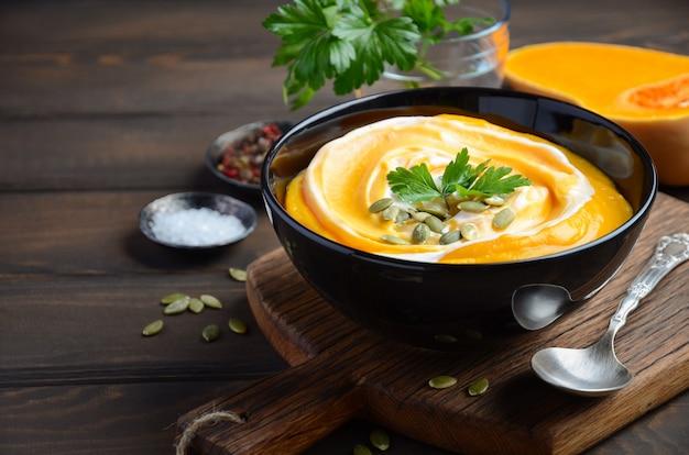 Тыквенный крем-суп с кремом и тыквенными семечками на деревянный стол.
