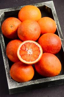 暗い木製トレイのブラッドオレンジ。